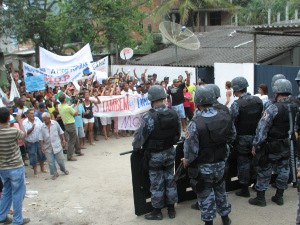 Riot police watch as residents display signs and banners