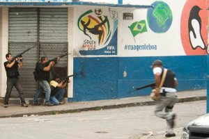 Police cover a street corner in front of the World Cup 2010 logo