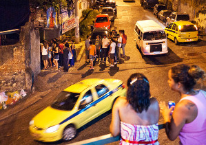 Favela residents in Vidigal watch at the entrance of the Lamparina party