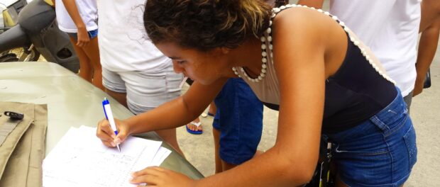 Ananda Trajano, a 15-year-old student and member of Coletivo Papo Reto, signs the petition for the implementation of an IFRJ in Complexo do Alemão.