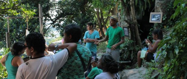 Kadão Costa, from the Nega Vilma Ecomuseum, tells the story of Vilma and Santa Marta to a group of visitors to the Ecomuseum.