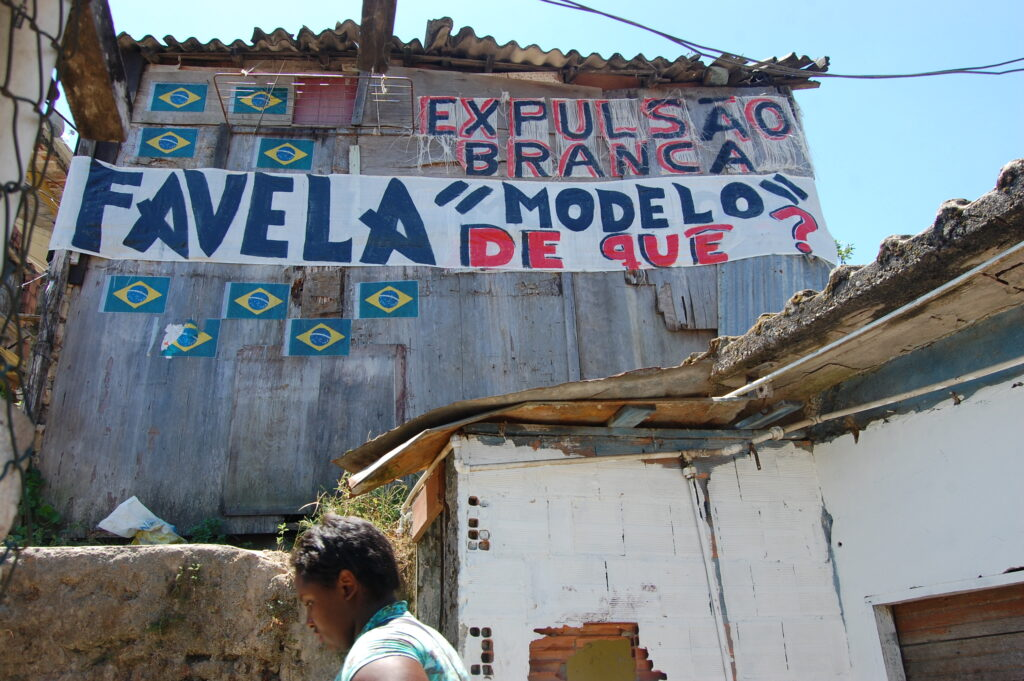 "The phrases ""Favela 'model' of  what?"" and ""White eviction"" (local term for 'gentrification') on a house in Santa Marta demonstrate the dissatisfaction of the residents. Photo by Miriane Peregrino"