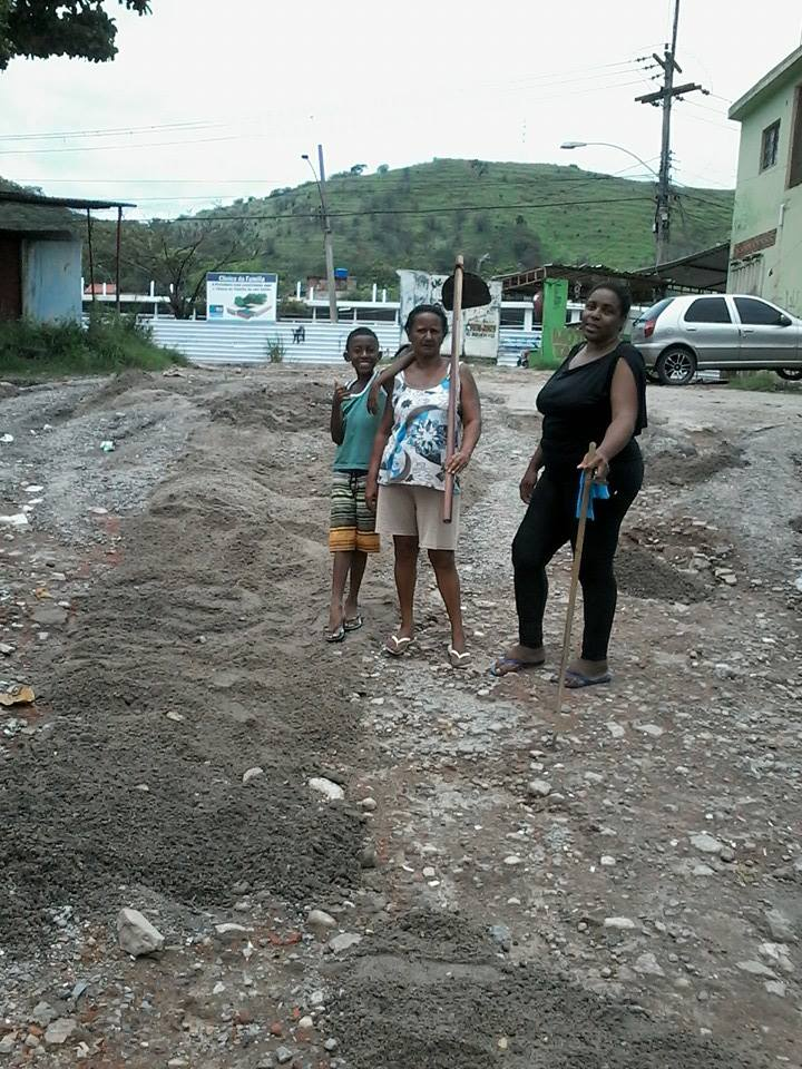 Dona Aldiceia (holding the shovel) and Catia Maria de Andrade clean up their community.