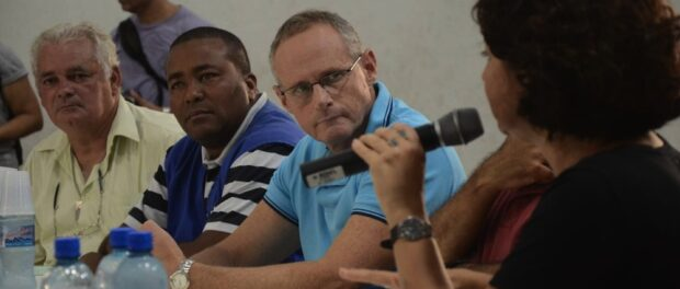 Betrame listens to Eliana during a public meeting at Maré in April 2014. Photo by O Globo