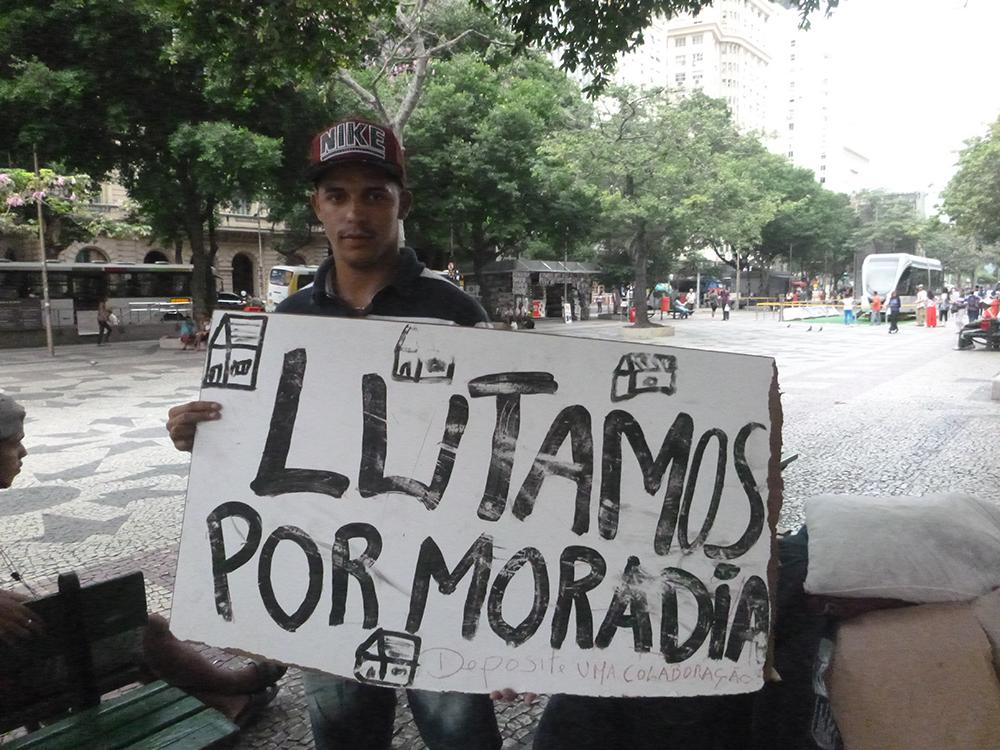 """Eduardo Felipe Aparecido Cunha holds up a sign: """"We are fighting for housing."""" Photo: Christine Wilkes"""