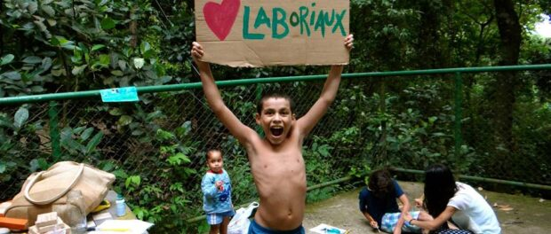 "Child holding a sign that reads ""I Love Laboriaux."""