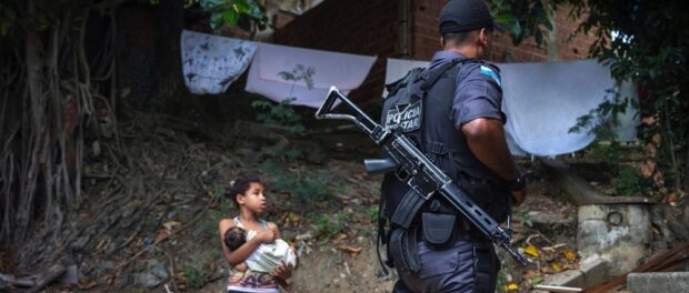 Police officer passes a young resident of Lins following the occupation of the community. Photo by Luiz Baltar / Imagens do Povo