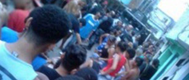 Bystanders look over Rodrigo's body in the street. Photo: Alemão Notícias