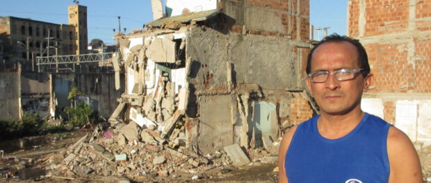 Lélio Fernandes stands in front of his half-demolished house