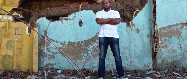 Pedro Henrique Berto in front of his damaged house in Vila Autódromo