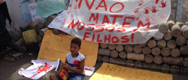 """Boy with book sits in front of protest sign that reads """"Don't kill our sons!"""""""