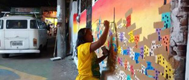Mariluce Mariá de Souza paints the walls of her community