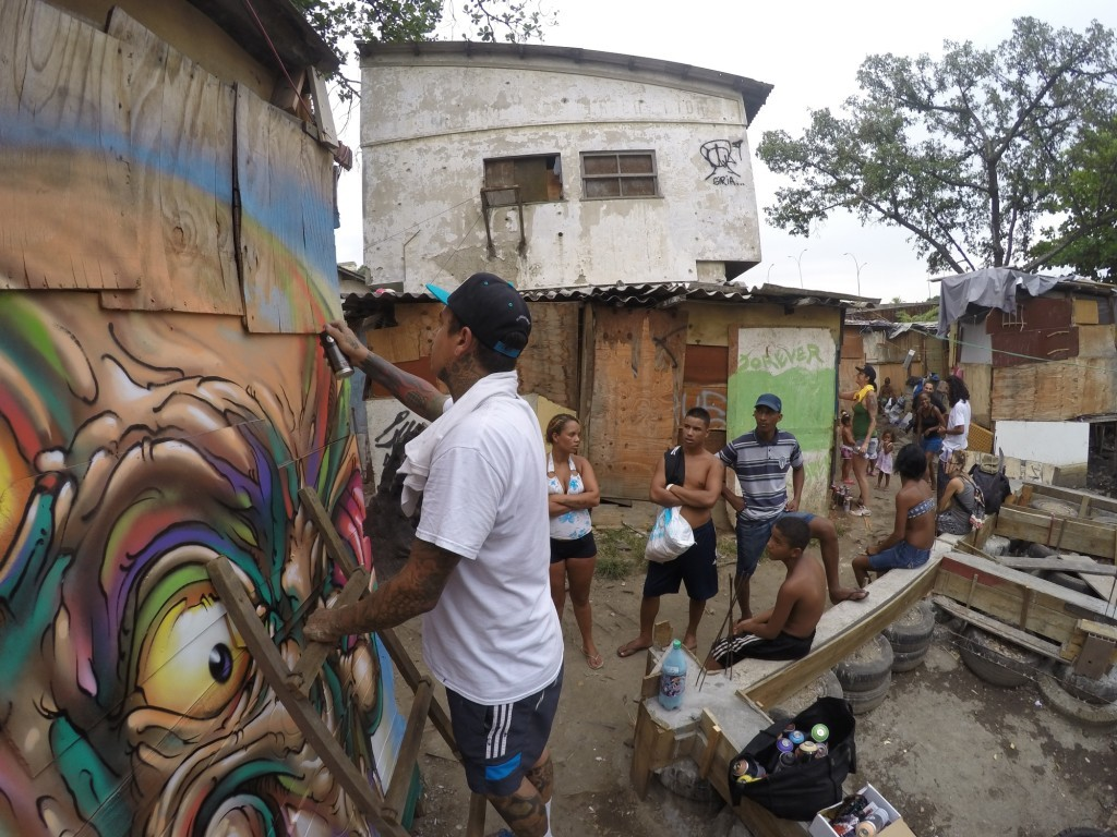 Graffiti artist Bruno Smoky from the Brasilândia favela in São Paulo contributes to artwork in Maré's newest favela. Photo by Monara Barreto, March 14, 2014.