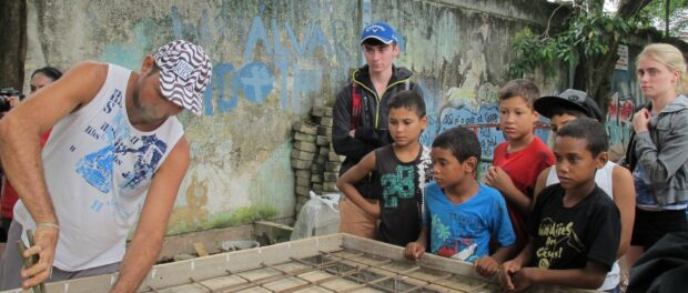 Community children anxiously watched as the Vila Autódromo ping pong table was built by residents