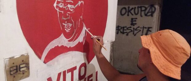 Occupier paints a portrait of Vito Gianotti, social movement leader after whom the occupation is named