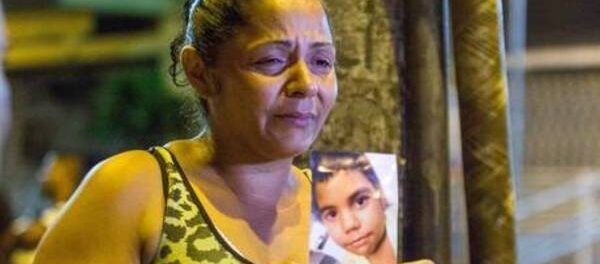 Tereza Maria de Jesus holds a photo of her son, Eduardo, killed by police in March 2015. Photo by Renato Moura