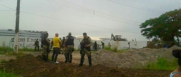 Shock Troops stand guard as the new fence is built. Photo from Vila Autódromo Facebook page