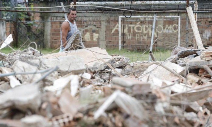 Altair Guimarães, president of the Residents' Association, looking at the rubble of his former home. Photo by Alexandre Cassiano / Agência O Globo