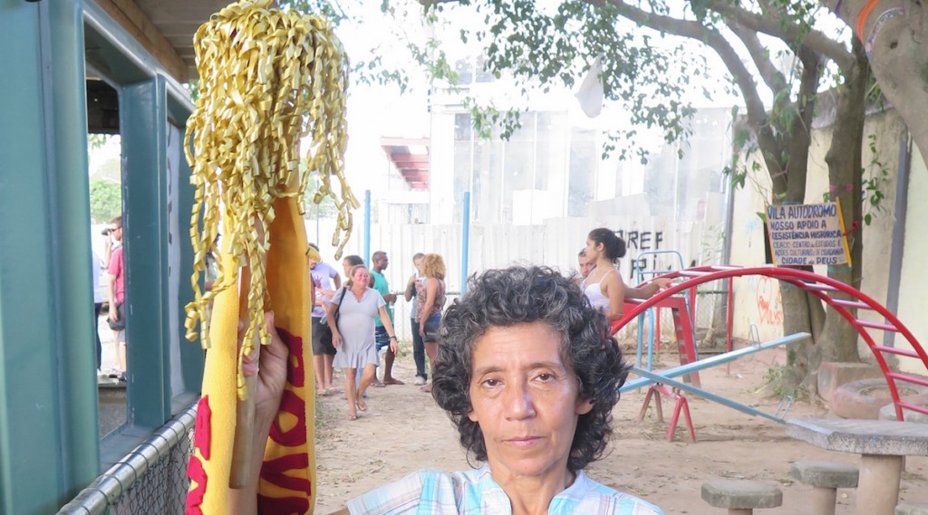 Maria da Penha holding Poverty Torch in the Parquinho before playground demolition