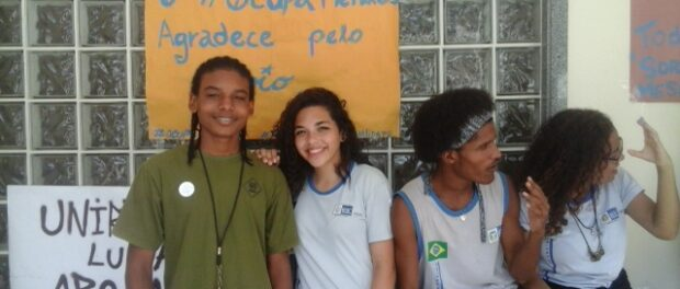 Students pose in front of signs at Mendes de Moraes