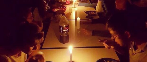 Students at Chico Anysio eat by candlelight after their school's electricity supplies are cut