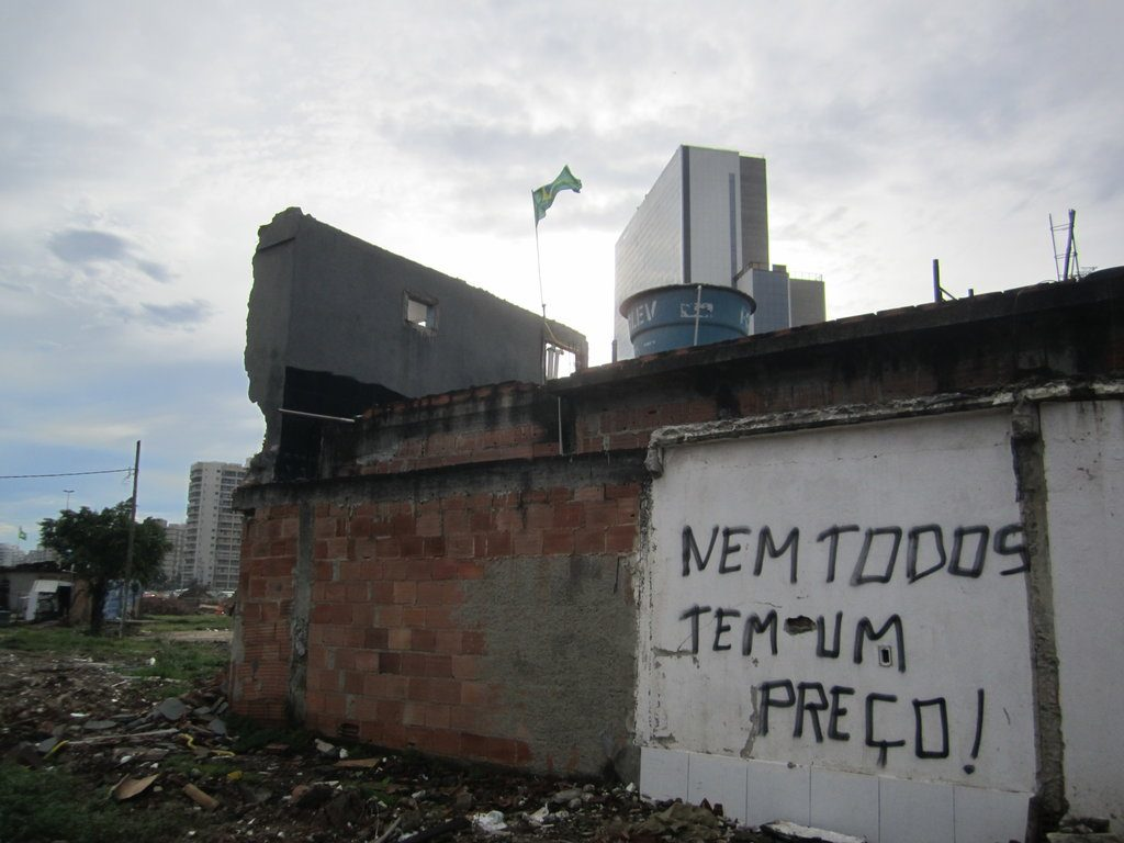 Demolished buildings in Vila Autódromo against Olympic hotel construction in the background