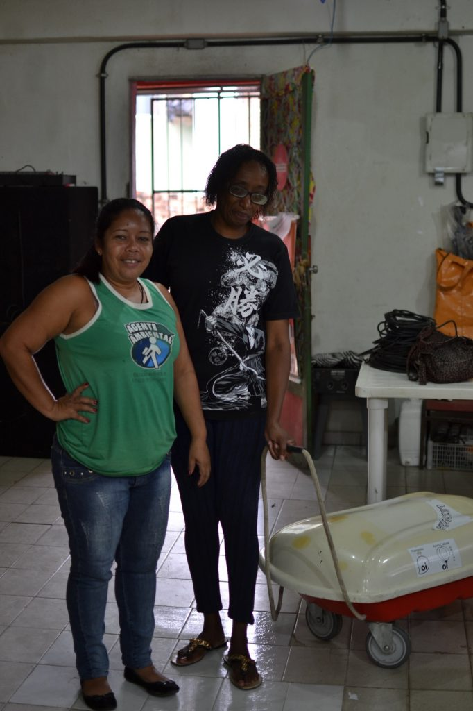 """Denise Vieira (left) and Denise Francisca (right) with the book cart used for the monthly """"Come Livros"""" event"""