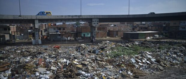 """Daily Mail image of a """"road passing over a favela"""" forefronts a heap of garbage."""