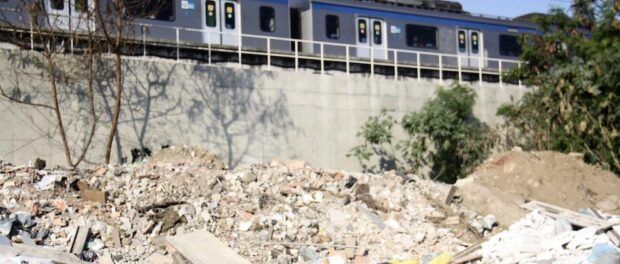 Piles of garbage and rubble lie under the train tracks in Beira Rio, Manguinhos.