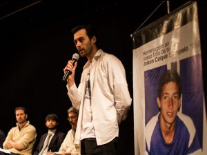 Davi Paiva addresses the public hearing next to a photo of deceased resident Jaison Caique Santos. Photo by Luis Felipe Marques
