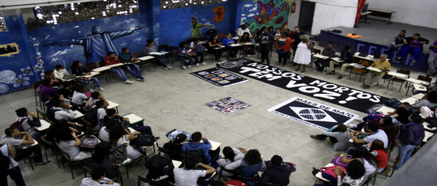 Activists place banners in front of panel on state violence, youth and racism. Photo by Natalie Southwick
