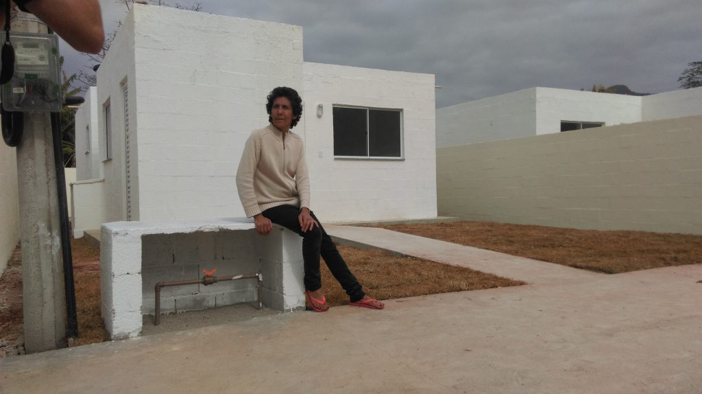 Maria da Penha sits outside her new home