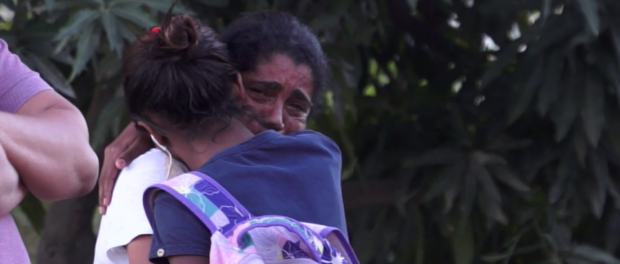 Naomy and her mother hug, crying, as they watch houses in Vila Autódromo being demolished