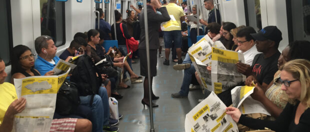 Commuters reading the PUC newspaper
