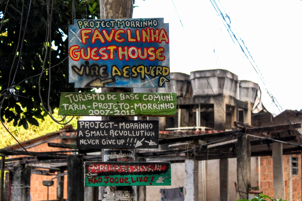 "Signs to Project Morrinho and the Favelinha Guesthouse reads ""A Small Revolution, Never Give Up!!!"" and ""Don't throw trash!"" Photo by Sophia Zaia"