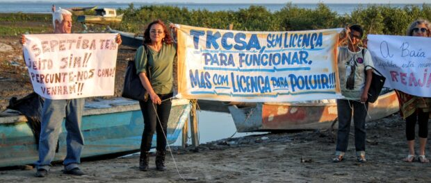 Activist Eliane Roxo holds a banner denouncing TKCSA's pollution of the bay