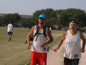 Edivandro runs at the Maré Olympic Village with an assistant
