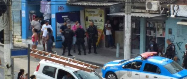 Santiago in pink shirt intimidated by police in Alemão