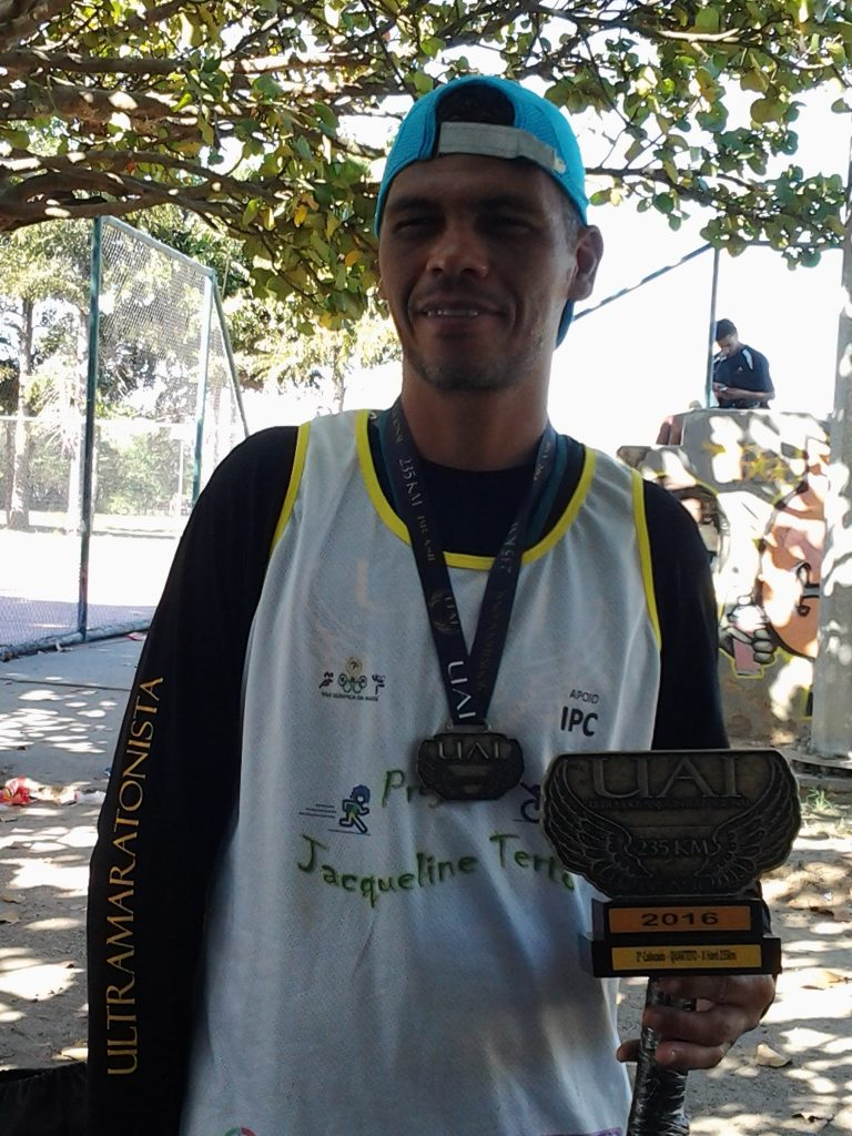 Edivandro with the medal and trophy he received for coming 2nd in the recent marathon