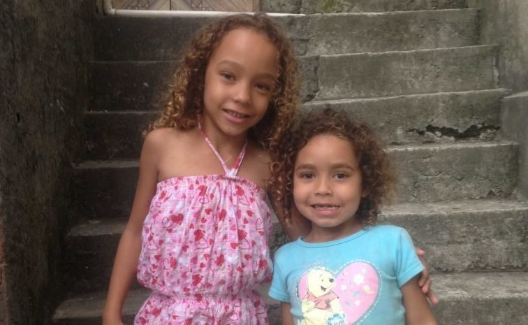 Two of Suzanna da Silva's daughters pose outside their home in Vidigal.