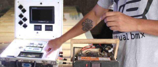 Fábio shows a presentation on his self-designed solar-powered briefcase presentation system