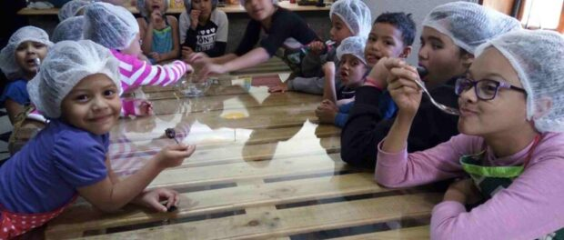 Children take a class on sustainable, healthy, vegetarian cooking hosted at the Favela da Paz kitchen as part of the Vegearte Project.