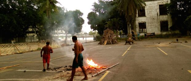 Tribal members engage in traditional rituals during the day, with the Maracanã stadium and old Indigenous Museum in the background