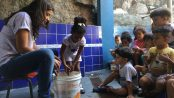 Sometimes a bucket full of soil is the most interesting thing: Elisângela (Horta Inteligente) planting seeds with kids from the Tia Dora daycare
