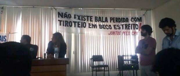 "One of the banners brought to the meeting by the Juntos Pelo Complexo (Together for the Complexo) reads ""There's no such thing as a stray bullet in a gun fight in a narrow alley!"""