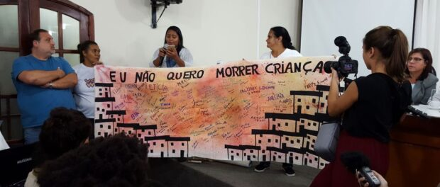 """Mariluce shows work created by children participating in the FavelArte project: """"I don't want to die young."""" Photo: RioRealBlog"""