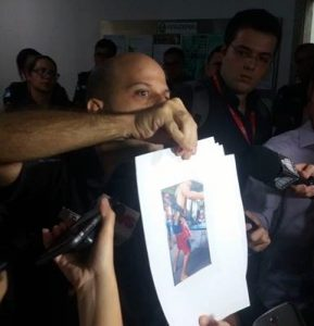 Captain Zuma, UPP captain for Nova Brasília, shows photos of armed traffickers.