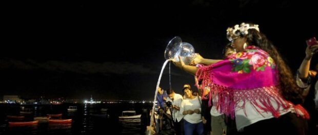 Attendees watch as the water they brought with them from home is poured into the Guanabara Bay. Photo by Domingos Peixoto from Agência O Globo