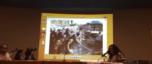 Resident and activist Sandra Maria presents photos of Vila Autodromo's struggle against state violence