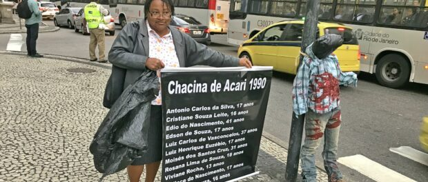 Ana Lúcia, of the Network Against Violence, holds sign honoring those dead in the Acari massacre of 1990
